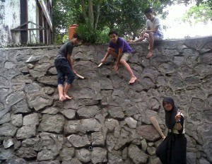 Mahasiswa mmebersihkan tebing batu depan perpustakaan sebagai kegiatan IAYP untuk pelayanan mashyarakat